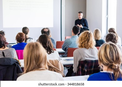 Person delivering a speach. Audience at a conference presentation.