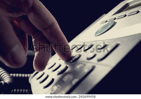 Person dialing out on a telephone punching in the numbers on the keypad with a finger, vintage effect toned image.