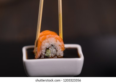 Person dipping a fresh salmon sushi roll in a small dish of soy sauce using chopsticks in a close up view on black