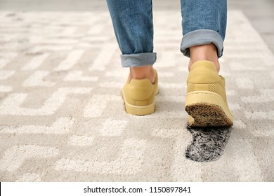 Person in dirty shoes leaving muddy footprints on carpet