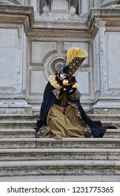 Person disguised in extravagant colorful dress with mask sitting on the stairs during the famous Carnival in Venice, Italy. The traditional festival is well known mainly for ist beautiful masks.
