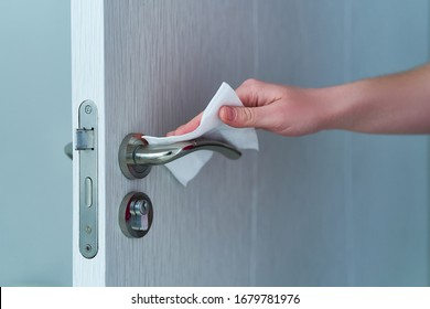 Person disinfects and cleans door handle with antibacterial wet wipes to protect against viruses, germs and bacteria during coronavirus outbreak and flu covid ncov epidemic. Clean home  - Shutterstock ID 1679781976