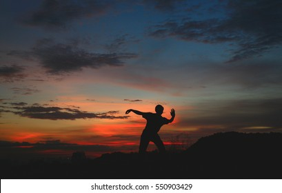 A person is doing Tai Chi. It is nightfall and there are colorful clouds in the sky.