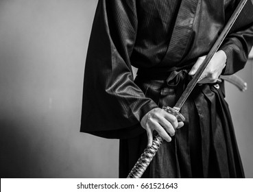 A person dressed up as Samurai action with Japanese sword black and white.