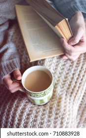 a person is  drinking coffee and reading a book