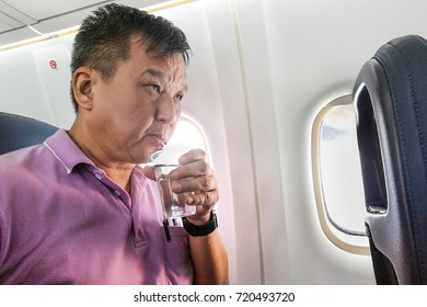 Person drinking water in airplane long haul flight to hydrate  himself from dehydration