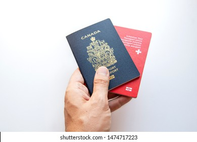 A person with dual citizenship holding a Canadian and a Swiss passport in his hand.