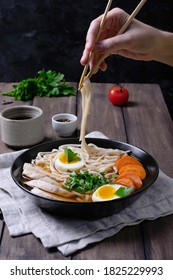 Person eating asian ramen soup with chicken