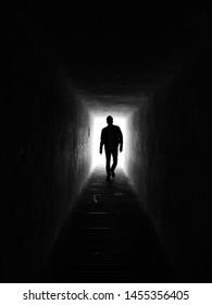 A person entering a dark passage.