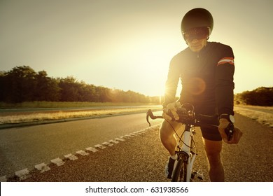 A person in the evening standing on an empty road and setting the bike.