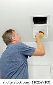 Person Examining Small Duct with a Flashlight. Homeowner looking into a small air duct searching for and dirt and examining the condition. Male examining the cleanliness of a small home HVAC air duct.
