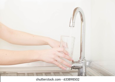 person filling up a glass of tap water on kitchen