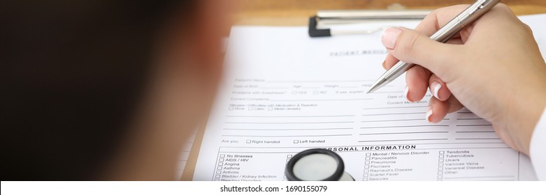 Person fills in a pen with document personal data. Doctor fills in patients personal data. Initial examination, stethoscope lies on table. Medical care, health status and patient diagnosis