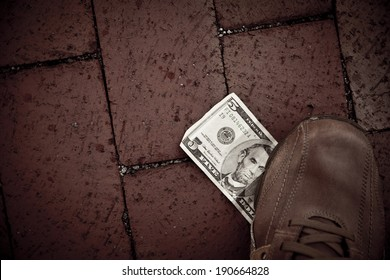 A person finds a US five dollar bill at the street and he uses his foot to step on it.