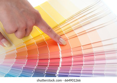 Person with a finger shows to the selected color in the palette for paint tinting. Colored catalog fan. The concept of choosing interior design.