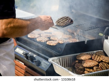 Person Flipping Burgers During BBQ Outdoors