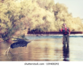 a person fly fishing in a river with a fly in the foreground vintage toned