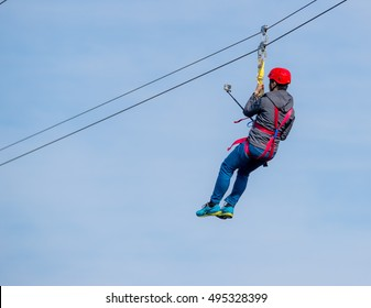 Person flying under a zip line. He is taking a selfie on the way across. His back is facing the camera so his face is not visible. The sky above is white/blue.
