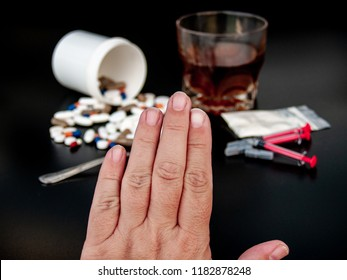 A person gesturing with his hand stop drugs, Pills of different sizes, shapes and colors, a glass of whiskey, drugs and syringes Concept of drugs and alcohol