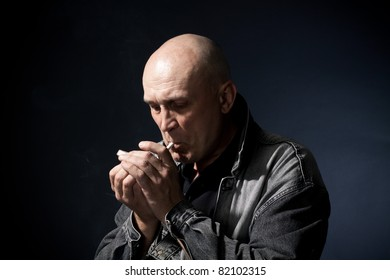 The person gets a light a cigaret on a black background