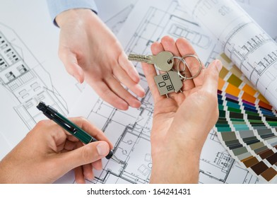 Person Gives A Key To Another Person With Blueprint Below