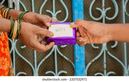 Person giving Gift to woman for vote in front of the door, concept of showing a Gift for vote.