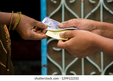 Person giving money to woman for vote in front of the door, concept of showing a cash for vote.