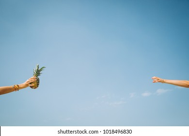 Person giving pineapple to another sky blue