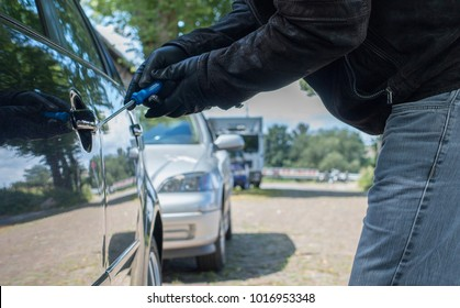 A person with gloves is trying to break the lock of a car on a street