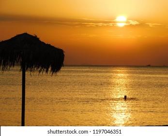 Person in a golden sunset near a beach in Glyfada, Greece