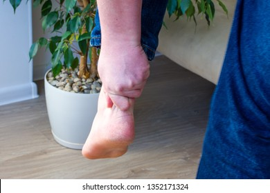 Person grabbed with hand of achilles tendon or heel cord due to severe pain. Concept photo of symptoms and disease and injury of achilles tendons such as gap, rupture, sprain, tendonitis, tendonosis
