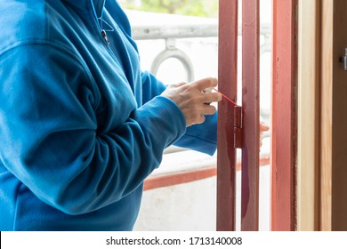 A person greases the door hinges with oil