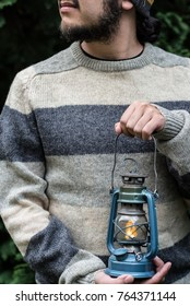 A person in a grey sweater holding an old lantern in a forest