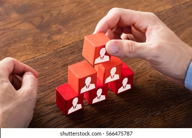 Person Hand Building A Blocks Of Team On Wooden Desk. Employee Recruitment Concept