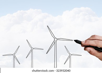 Person hand drawing windmills on sky background