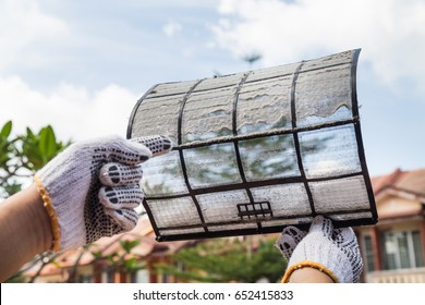 Person hand with glove pointing on thick dirty dust on air conditioner filter