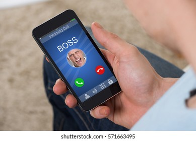 Person Hand Holding Mobile Phone With Angry Businessman Boss Calling