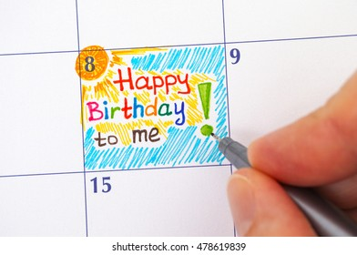 person hand with pen writing reminder happy birthday to me in calendar