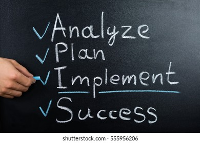 A Person Hand Showing Business Strategy Plan On Blackboard