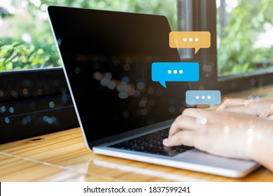 Person hand using laptop typing into chat, chatting conversation in chat bubble pop-up. Social media maketing concept.