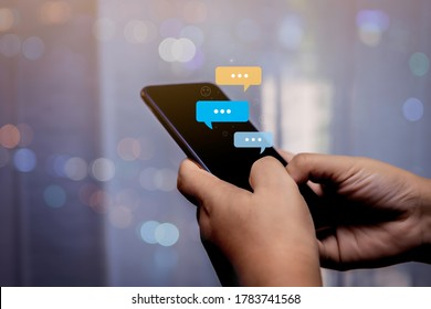 Person hand using smartphone typing, chatting conversation in chat bubble pop-up. Social media maketing concept.