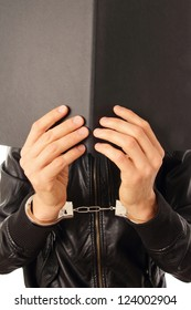 Person in Handcuffs and folder in front of his face