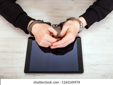 Person in Handcuffs with a Tablet Computer on the Table closeup