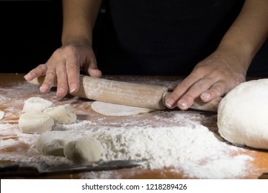 Person handling a dough with a rolling pin floured table