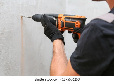person hands hold hammer drill close up