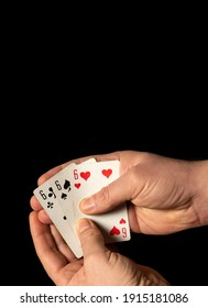 Person hands are holding playing cards three sixes close up on black background