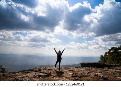 A person hands up standing on rocky mountain looking out at scenic natural view and beautiful blue sky