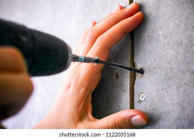 Person hands using screw drill. Close-up.