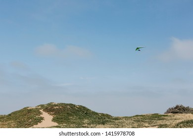 A person hang gliding on a clear day with the ground in the background