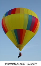 Person Hanging From a Colorful Hot Air Balloon High in the Sky